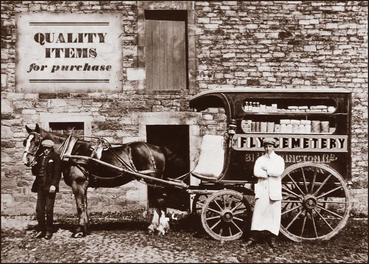 Dark sepia photograph of a stationary horse and wagon, a window in the side of the wagon reveals various bottles, jars, boxes and bags lined up on two shelves.  On the wall behind the horse and wagon is a sign bearing the text: Quality Items for Purchase