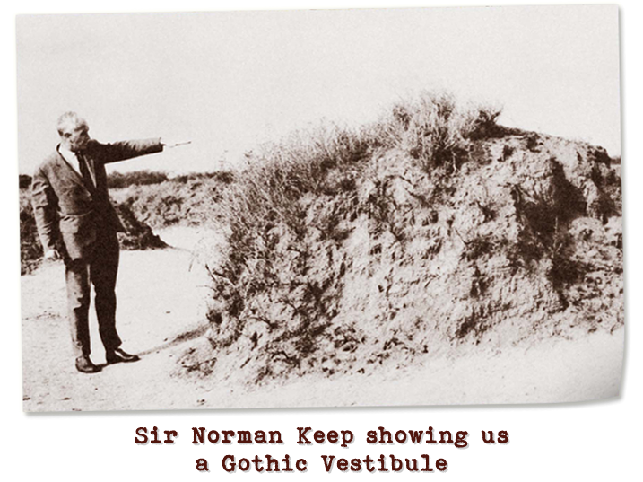 Black and white photograph of an older gentleman pointing towards a dirt mound partially covered with grass.  Captioned: Sir Norman Keep showing us a Gothic Vestibule